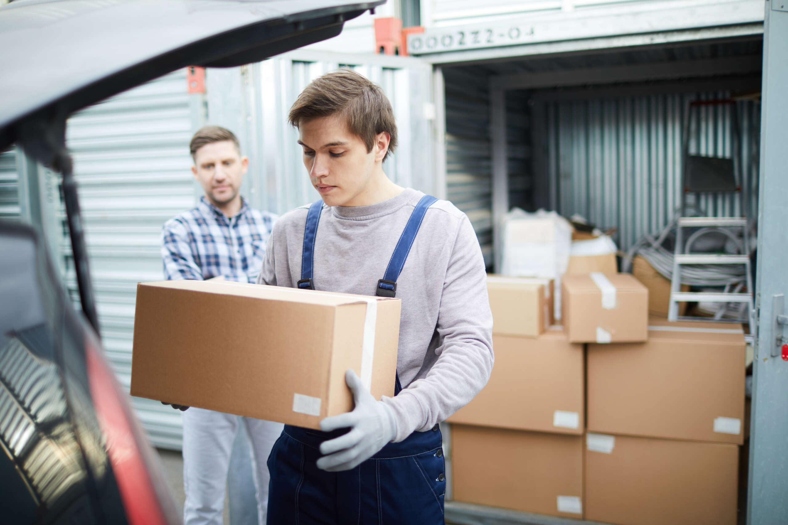 Serious young male mover carrying cardboard box from large container with stacking stuff while loading car for client outdoors
