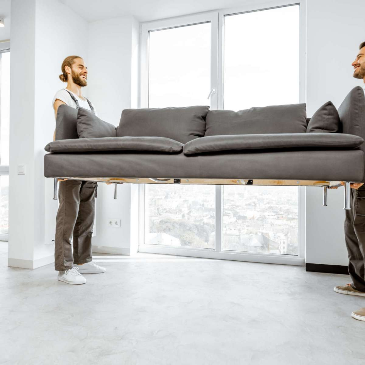 Two professional movers in workwear placing large couch in the living room of the modern white apartment. Furniture delivery concept
