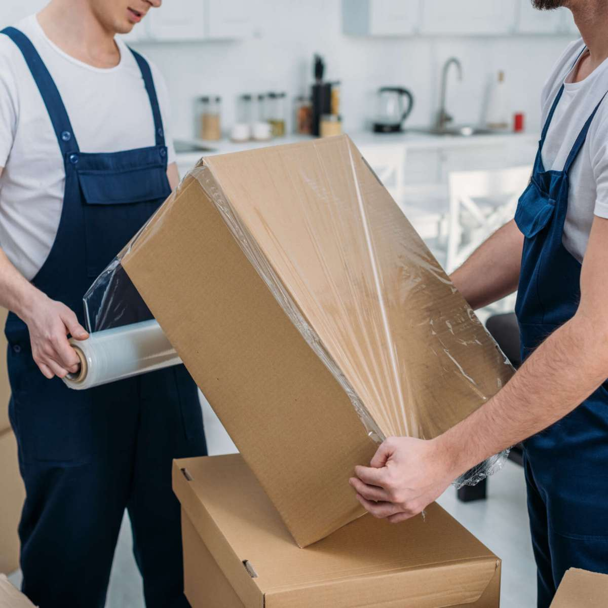 partial view of movers wrapping cardboard box with stretch film in apartment