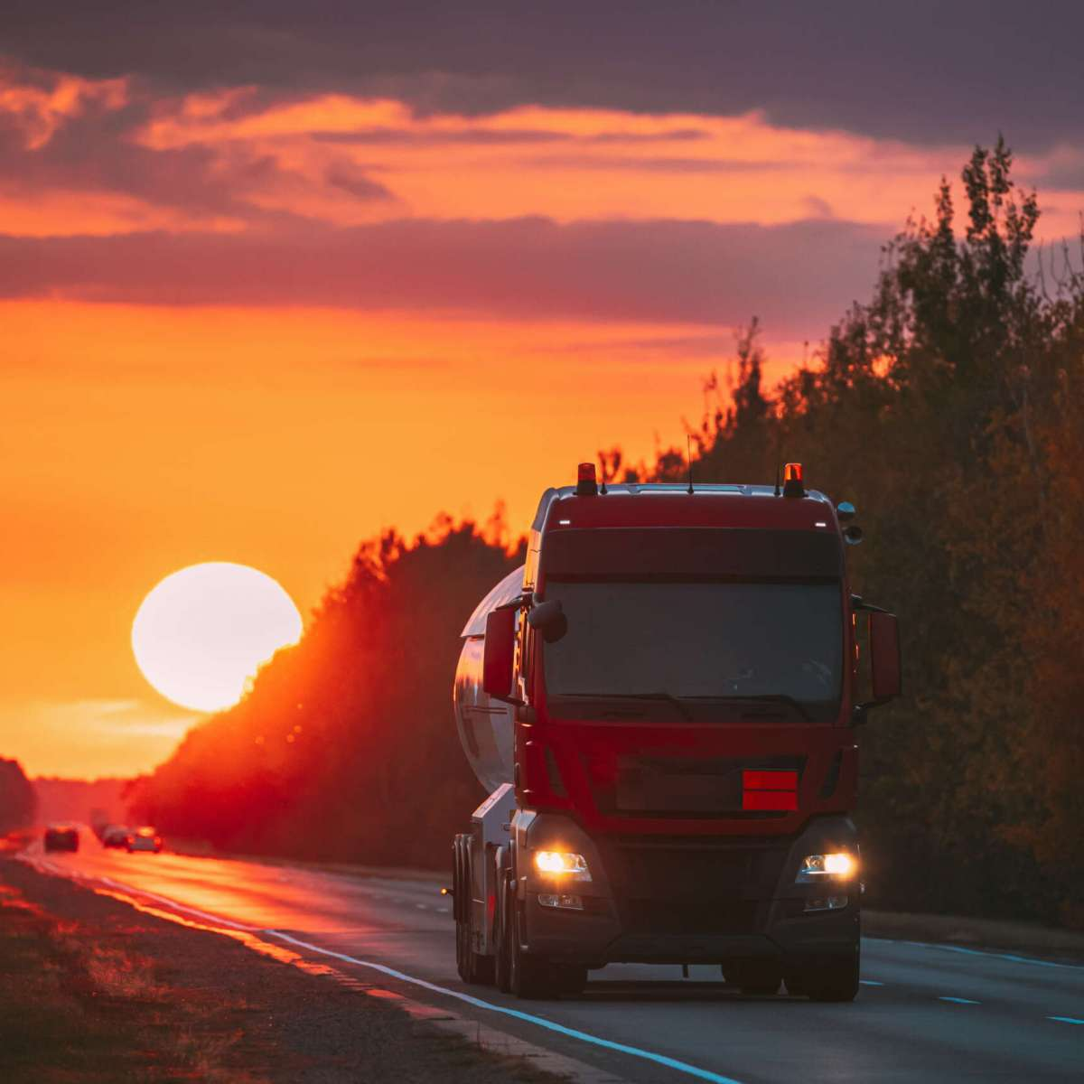 Red Truck Or Tractor Unit, Prime Mover, Traction Unit In Motion On Road, Freeway. Asphalt Motorway Highway Against Background Of Big Sunset Sun. Business Transportation And Trucking Industry